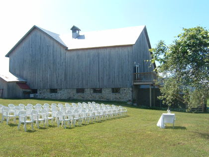 Shown here is a basic set up for an outdoor ceremony. The barn wall is great for a wedding party to line up or come down the staircase for a short march to the apple trees & grape vines.