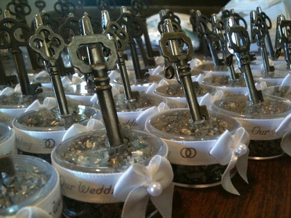 I made the escort card holders out of fake skeleton keys, bead containers, metallic rock chips, ribbon and gator clips. These were also given away as one of our party favors. We also gave out bottle openers that look like antique keys. The Favors - Sara and Shaun's Wedding in Janesville, WI, USA