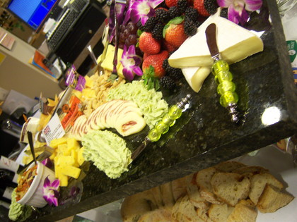Appetizer display featuring an assortment of cheeses and fruits from the catering department. -  - Grand Central Market & Deli