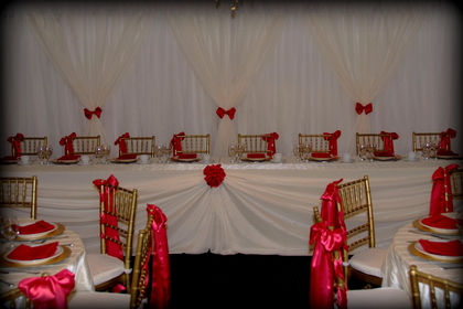 Ivory and Wildfire Red Head Table and full set up with Ivory Pin Tuck Overlay and Wildfire Satin Sash rentals - Flowers and Decor - Classic Weddings And Events