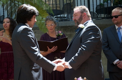 Margaret the officiant is reading the hour glass ceremony as Noel interprets in ASL and Xo looks on.  Vinny & Zack contemplate the words being read aloud and towards their future. The Ceremony - Zack and Vincent's Wedding in Oakland, CA, USA